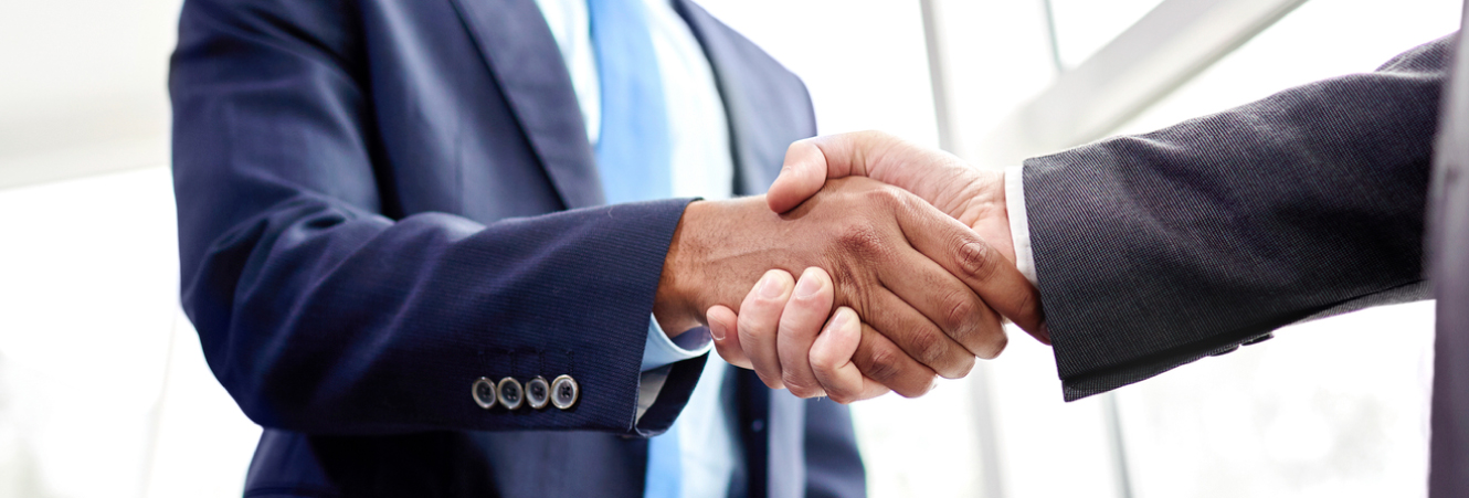 A close up of two suited business men shaking hands