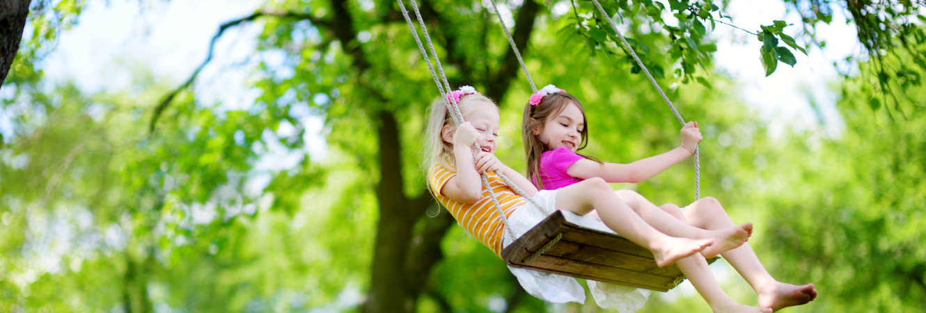 Two young girls swinging.