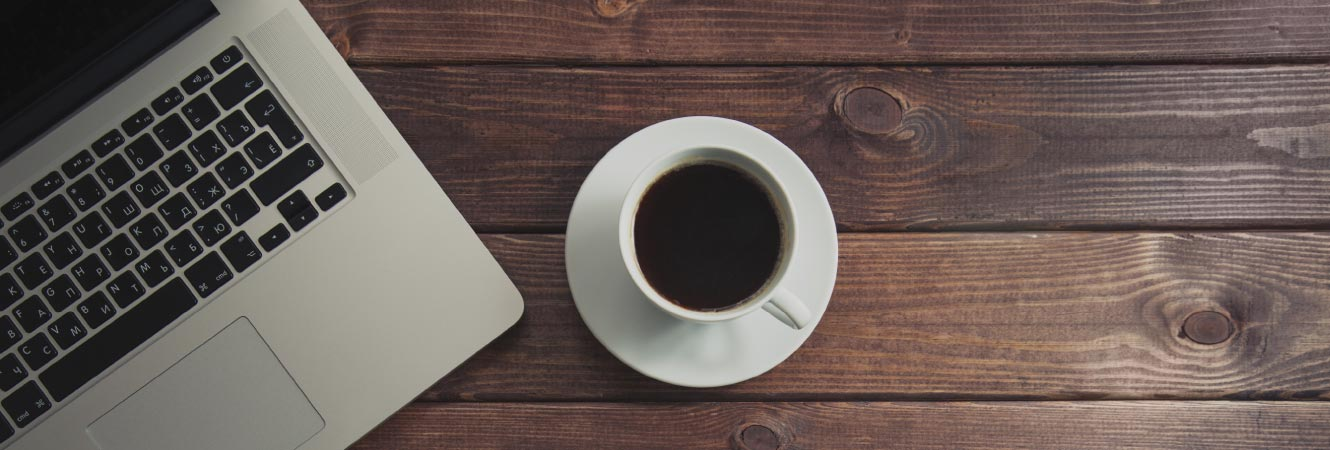 A cup of plain coffee by a laptop on a table