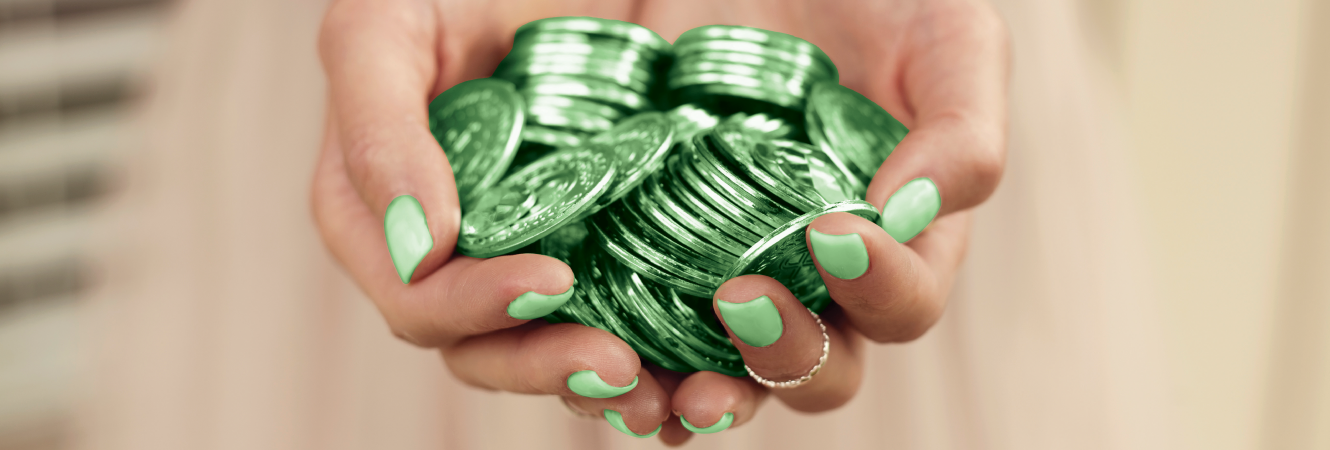 Hand holding green coins.