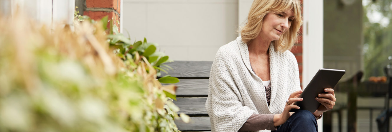 A mature woman sitting outside her home while using a tablet.